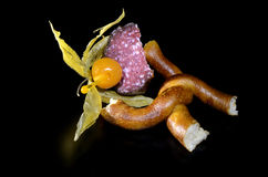 Pretzel and physalis pinned to sausage Royalty Free Stock Image