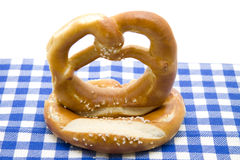Pretzel with salt. Baked foods pretzel on blue white table cloth royalty free stock images