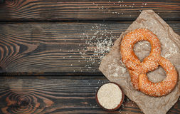Pretzel with sesame seeds on the dark wooden table Royalty Free Stock Photo