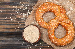 Pretzel with sesame seeds on the dark wooden table Royalty Free Stock Photos