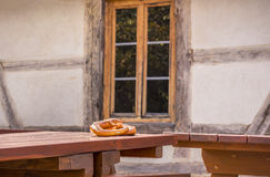 Pretzel on table in a rustic German decor. Two pretzels, a specific German pastry product, on a wooden table, in front of an old  rustic house, with German Stock Photo