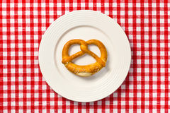 Pretzel on white plate Stock Images