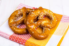 Pretzeles bávaros con las semillas de sésamo en los tableros blancos Imagenes de archivo
