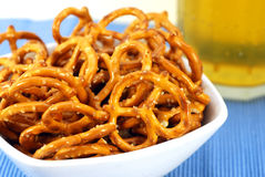 Pretzels and Beer. Bowl of pretzels with beer on a blue place mat Royalty Free Stock Image