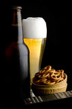 Pretzels with beer and remote control. On black background Stock Image