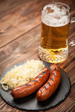Pretzels, bratwurst and sauerkraut on wooden table. Traditional german food of pretzels, sauerkraut, bratwurst and beer on wooden table Stock Images