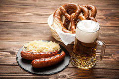 Pretzels, bratwurst and sauerkraut on wooden table. Traditional german food of pretzels, sauerkraut, bratwurst and beer on wooden table Stock Image