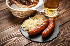 Pretzels, bratwurst and sauerkraut on wooden table Royalty Free Stock Images