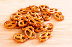 Pretzels on a light wooden board. Bright yellow and orange crispy crackers and pretzels are on a light wooden board. Selective focus stock photos