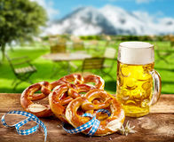 Pretzels and pint of beer to celebrate Oktoberfest. Pretzels and frothy pint of beer in a glass tankard to celebrate Oktoberfest served on a rustic wooden table royalty free stock images