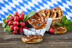 Pretzels and radishes. Fresh Bavarian pretzels in a breadbasket and a bunch of red radishes on a wooden table, in the background the white-blue flag of Bavaria Royalty Free Stock Photography