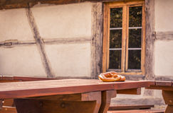 Pretzels on rustic table and German house background. Traditional German pastry treat, two pretzels on a wooden table with a medieval architecture house in the Royalty Free Stock Image