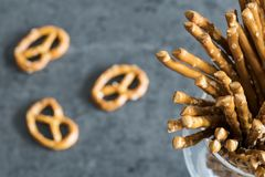 Pretzels and salted sticks in glass. Close up of salted party sticks and pretzels, against dark background stock photos