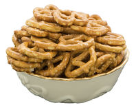 Pretzels snack foods bowl isolated white. A full bowl of salted twisty pretzels shows the concept of a salty American junk food diet Stock Image