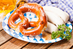 Pretzels, white sausages and a beer on a wooden table Royalty Free Stock Photography