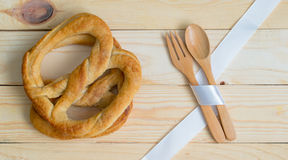 Pretzels and wooden kitchenware. Pretzels place besides wooden kitchenware, spoon and fork, on wooden table Stock Photography