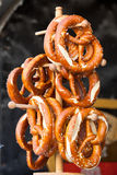 Pretzels on the wooden stand. Pretzels - traditional german snacks are hanging on the wooden stand Stock Photos