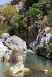 Preveli klyfta var det finns palmträd och floden Arkivfoton