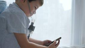 Prevención de la tos, niño en máscara de un inhalador con el teléfono móvil en las manos en sitio almacen de metraje de vídeo