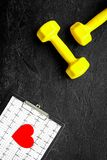 Prevent heart disease. Heart sign, cardiogram and dumbbells on black background top view copyspace Stock Images