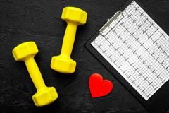 Prevent heart disease. Heart sign, cardiogram and dumbbells on black background top view Stock Photography