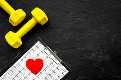 Prevent heart disease. Heart sign, cardiogram and dumbbells on black background top view copyspace Stock Image