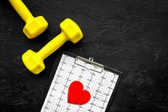 Prevent heart disease. Heart sign, cardiogram and dumbbells on black background top view copyspace Royalty Free Stock Photo