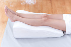 Preventing varicose vein. A woman's legs lay down on a pillow for relaxing and preventing varicose vein royalty free stock images