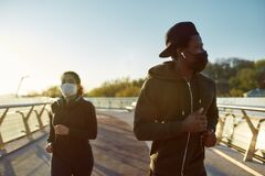 Free Preventing Virus. Young African Man And Woman In Medical Masks Running On The Bridge During A Pandemic. Sport And Stock Images - 184113254