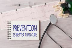 Prevention is Better than Cure. Written on notebook with stethoscope, syringe and pills. Medical concept stock images
