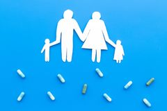 Prevention of diseases. Medicine for family health. Color pills near silhouette of family on blue background top view.  Royalty Free Stock Image