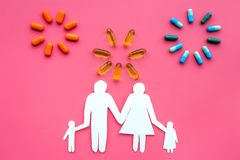 Prevention of diseases. Medicine for family health. Color pills near silhouette of family on pink background top view.  Stock Photos