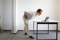 Prevention in office work, exercises. Exercise during office work - man with tablet in his office Stock Photos