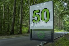 Prevention radar, speed limit detection device, digital alert sign - It shows green happy face and speed limit 50 on a street. Trough a forest royalty free stock photos