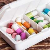 Preventivpillerar av olika färger i en ask Arkivfoto