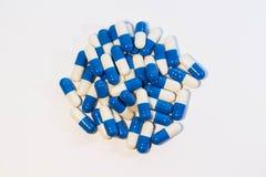 Preventivpillerar för en handfull Vita kapselläkarbehandlingar och blå medikament arkivfoton