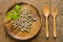 Preventivpillerar i trämaträtt och spill från flaskan Royaltyfria Bilder