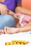 Preventivpillerar med en sjuk flicka på bakgrunden royaltyfri fotografi