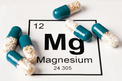 Preventivpillerar med mineralisk Mg-magnesium på en vit bakgrund med royaltyfri foto