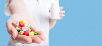 Preventivpillerar, minnestavlor och droger i doktorshand royaltyfria bilder