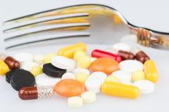 Preventivpillerar och äta middaggaffel Royaltyfria Bilder