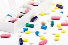 Preventivpillerar och kapslar i och ut ur preventivpillerorganisatör Arkivfoto
