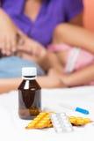 Preventivpillerar, termometer och en sjuk flicka royaltyfri foto