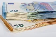 Preventivpilleren av räkningar skyler över brister 20 och 50 eurosedlar på vit bakgrund Royaltyfria Bilder