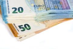 Preventivpilleren av räkningar skyler över brister 20 och 50 eurosedlar på vit bakgrund Arkivfoto