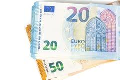 Preventivpilleren av räkningar skyler över brister 20 och 50 eurosedlar på vit bakgrund Royaltyfri Fotografi