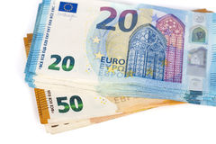 Preventivpilleren av räkningar skyler över brister 20 och 50 eurosedlar på vit bakgrund Royaltyfria Foton