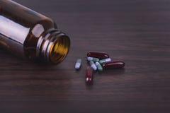 Preventivpillerflaska med olika preventivpillerar och kapslar på träbakgrund Fotografering för Bildbyråer