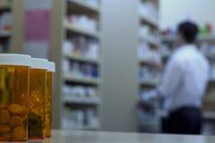 Preventivpillerflaskor på ett apotek kontrar med apotekaren i bakgrund Royaltyfri Foto
