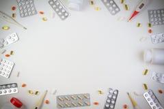 Preventivpillergränsbakgrund Vitaminer minnestavlor, preventivpillerar i flaskor för drog för blåsapacke, termometrar på vit bakg Arkivbild